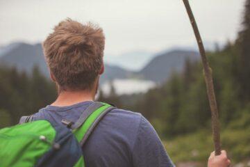 Wanderer mit grünem Rucksack und Wanderstock in Rückenansicht