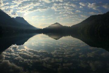 Bergkulisse spiegelt sich doppelt im See
