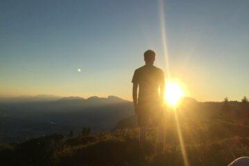 Mann steht auf Gipfel und schaut direkt in untergehende Sonne