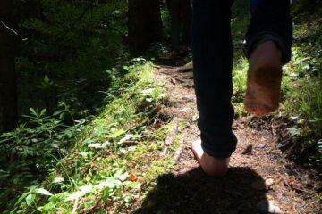 Mann läuft barfuß auf Waldboden