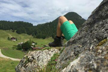 Person ruht sich mit angewinkelten Beinen in grüner Hose am Berg lehnend aus