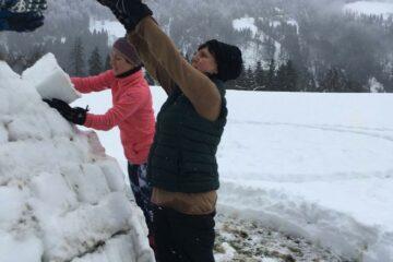 Zwei Frauen bauen ein Iglu