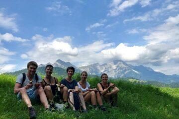 Teilnehmer sitzen auf Wiese vor Bergkulisse