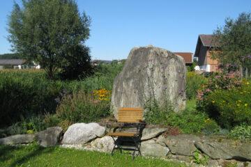 Stuhl vor riesigem Stein im Garten