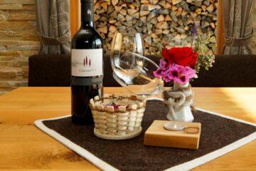 Tisch mit Wein, Glas, Körbchen und Blumen