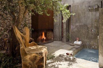 Innenhof mit Feuerstelle, Wasserbecken und massivem Holzstuhl unter Baumdach