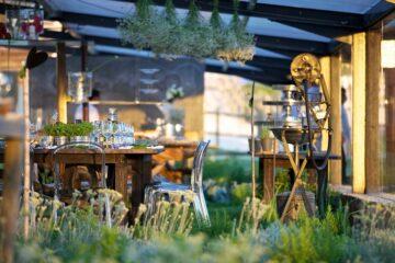 Essgelegenheit inmitten grüner Bepflanzung und hängenden Blumensträußen