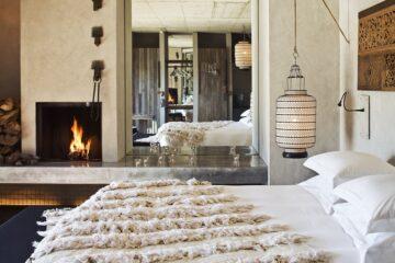 Bett mit Felldecke und Kamin vor großem Spiegel