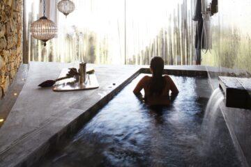 Pool mit Dame in Rückenansicht vor Fensterfront