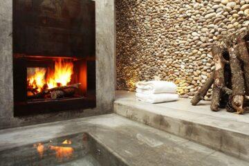 Offener Kamin, Wasserbecken, Steinwand und Holzelement in einem Raum