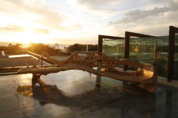 Beleuchtete überdimensionale Wurzel in Pool mit Meerblick im Abendrot