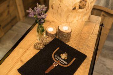 Kerzen und Rucksacktasche auf Holz-Sideboard