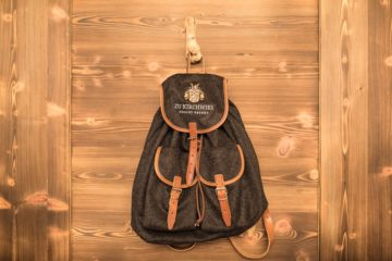 Rucksack in Bergsteigeroptik hängt an Holzwand