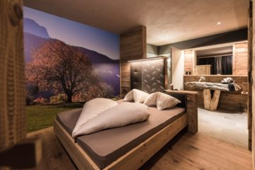 Bett mit Bettdecke in Herzform gefaltet in Lodge