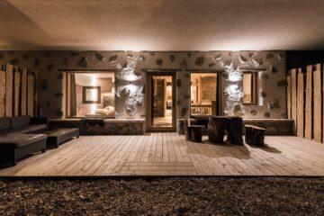 Blick auf Holzterrasse in beleuchtete Lodge