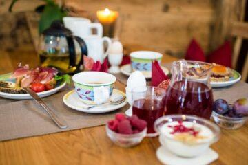 Tisch mit Frühstücksgeschirr, Marmelade, Joghurt und Ei