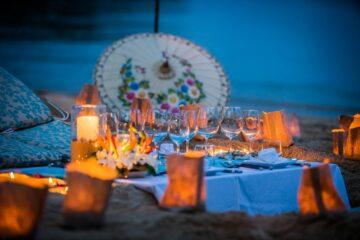 Kerzen in Tüten und Schirmdekoration auf dem Strand