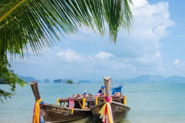 Zwei Longtailboota liegen am Strand
