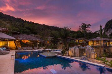 Pool und beleuchtete Villen im rosa abendhimmel
