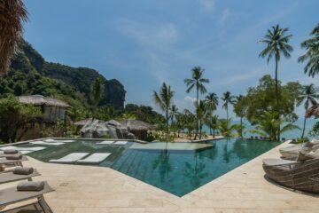 eckiger Pool mit Liegen und Palmen