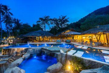 beleuchteter Pool mit Restaurant im Hintergrund