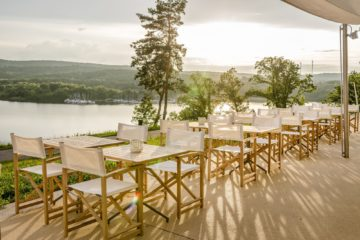 Terrasse mit Blick auf See und Sitzgelegenheiten in der Morgensonne