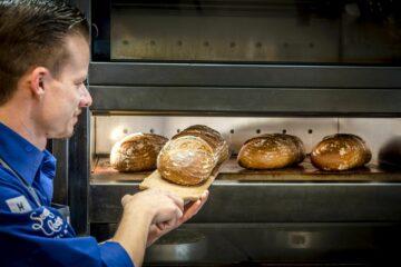 Mann holt frisch gebackenes Brot aus dem Ofen
