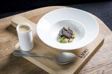 Schwarze Wurst auf Gemüse und Suppe im Kännchen