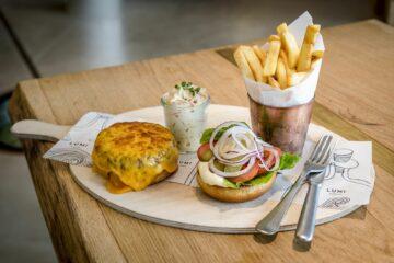 Holzbrett mit überbackener Frikadelle, belegtem Burgerbrötchen, Pommes Fries und Salat im Glas