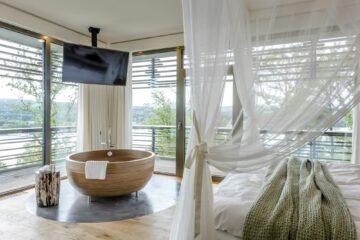 Badezuber aus Holz vor Fensterfront neben dem Himmelbett