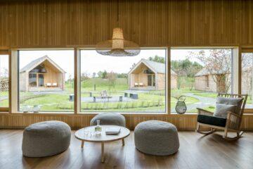Sitzgelegenheit mit Sofahockern vor Fensterfront zu Saunahäusern