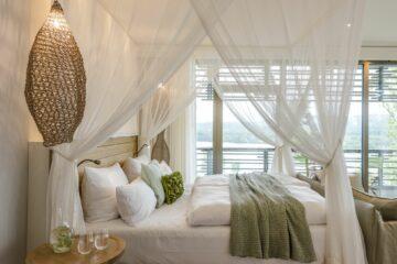 Himmelbett mit Kissen in wieiß mit grünen Kissen