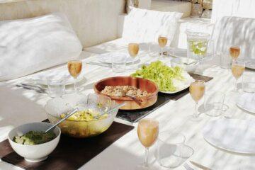 Weiße Sitzecke mit Prosecco und Schüsseln in der Tischmitte