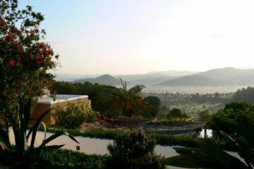 Blick von Terrasse auf Blütensträucher und Meer