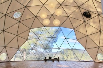Gläserner Kuppelbau mit Holzboden