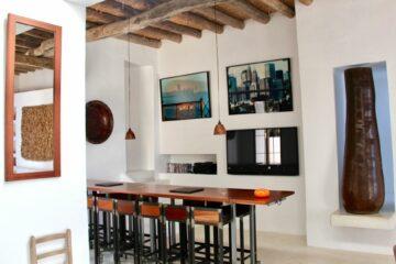 lange Bartheke mit Stühlen und Bilder an der Wand