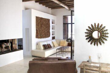Wohnfläche mit Sofas und Sonnenskulptur an der Wand