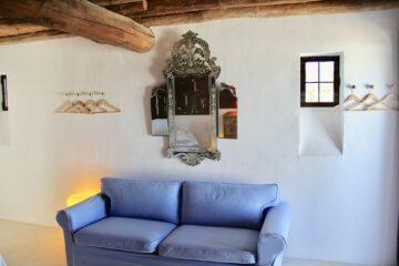 Hellblaue Couch vor Spiegel mit Ornamenten