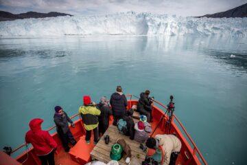 Passagiere auf Boot schauen auf weiße Gletscherwand
