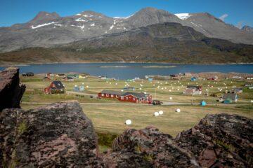 Blick auf Wasser und rote Häuser vor Bergkulisse