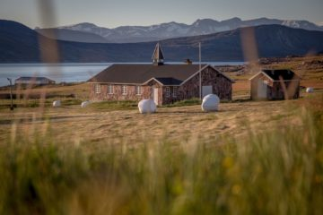 Kirche aus Tein vor Bergkulisse und Fjord