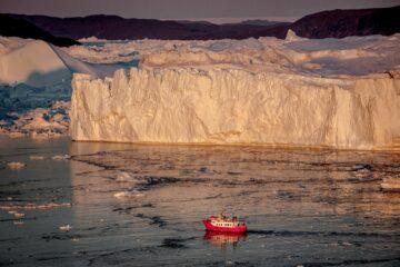 Rotes Schiff hebt sich vor großer Eiswand ab in orangenem Licht