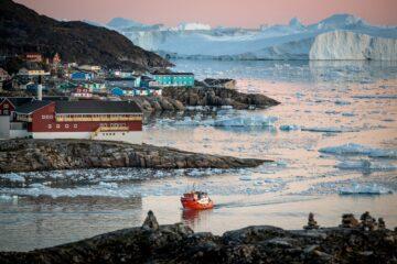 Häuser und Boot vor Inlandeis in rosa Licht getaucht