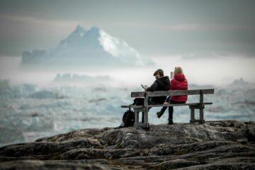 Zwei Personen auf Holzbank mit roter und schwarzer Jacke vor weißem Berg