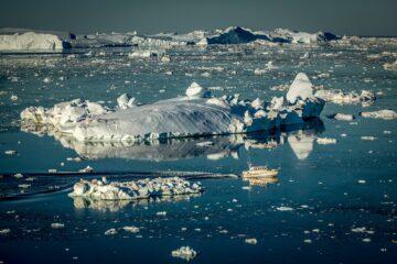 Kleines weißes Boot inmitten von schwimmendem Eis