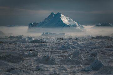 Weißer Berg vom Nebel umhüllt auf weißer Eisfläche