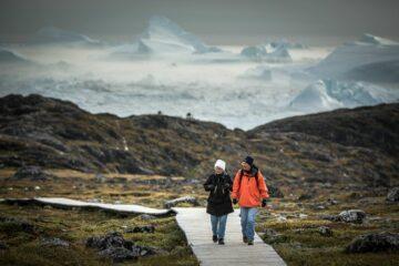 Mann in orangenem Anorak und Frau mit weißer Mütze wandern auf Weg durch Felsenlandschaft