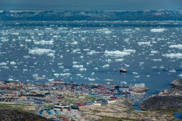 Bunte Häuser aus der Ferne und Bucht mit Eis als weiße Sprenkel auf dem Blau des Wassers