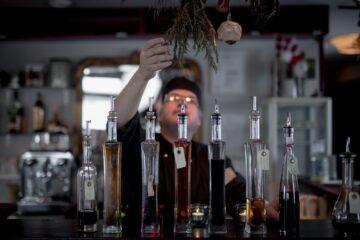 Mann greift nach Kräutern an der Decke vor Tisch mit Glasflaschen