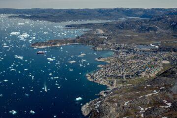grün-braune Küste mit Städten als Punkten und blauer Fjord von oben